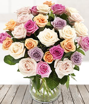 vase arrangement bursting with mixed roses and spr