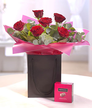 six red roses in a gift bag aquapack delivered by